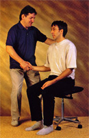 Teacher helping student to detect and release muscular tension while sitting. This results in a more relaxed and upright posture.