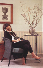 Woman leaning back on a chair while on the telephone