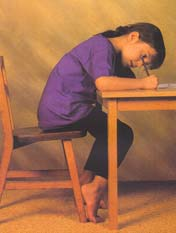 Picture of child bending over a school desk. Many hours of this can cause back problems and poor posture
