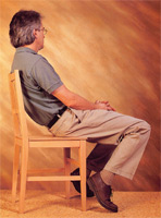 Man leaning back in a chair. This type of misuse of the body can cause severe back pain over time.