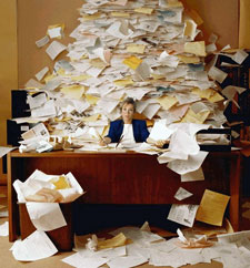Overwhelmed office worker at desk covered with mountain of papers