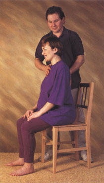 Alexander Technique teacher helping a pregnant woman with her posture while sitting