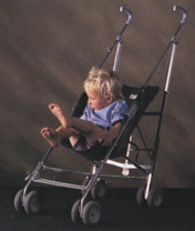 Young child struggling to get comfortable in a typical backward sloping pushchair