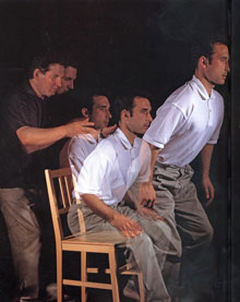 Strobe photograph of man rising from chair, guided by Alexander Teacher