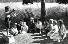 Children gathered round a child on a soapbox